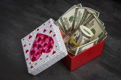 Stos dolary w czerwonym prezenta pudełku fotografia stock