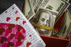 Stos dolary w czerwonym prezenta pudełku obraz stock