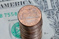 Stos jeden USA centu monety na jeden dolarowym rachunku Zdjęcie Royalty Free