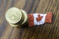 Stos kanadyjczyk jeden dolara monety z kanadyjczyk flagą obraz stock