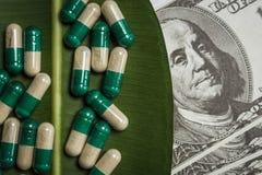 Stos kapsuły na zielonym liściu blisko dolarów zdjęcia royalty free