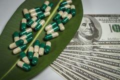 Stos kapsuły na zielonym liściu blisko dolarów obrazy stock