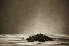 Stos kawowe fasole na drewnianym stole naprzeciw defocused burlap Zdjęcia Stock