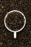 Stos kawowe fasole w białej filiżance z kawowymi fasolami w tle zdjęcie royalty free