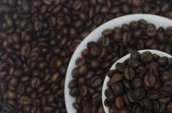 Stos kawowe fasole w białym spodeczku w 3 warstwach i filiżance zdjęcia royalty free