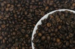 Stos kawowe fasole w białym spodeczku z fasolami w tle Zdjęcia Royalty Free