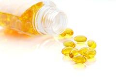 Stos omega 3 rybiego oleju kapsuły rozlewa z butelki Fotografia Stock