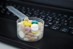 Stos pigułki w plastikowej pomiarowej łyżce na klawiaturze obrazy stock