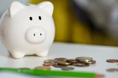 Stos różne monety blisko białego piggybank na stole Obrazy Stock