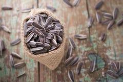 Stos słonecznikowi ziarna na drewnianym tle Zdjęcia Stock