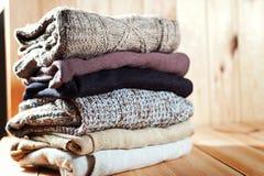 Stos trykotowa zima odziewa na drewnianym tle, pulowery, przestrzeń dla teksta Fotografia Stock