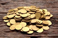stos złocista moneta na drewnianym tle pieniężnym i oszczędzaniu obraz royalty free