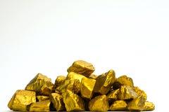 Stos złociste bryłki lub złocista kruszec na białym tle, cenny zdjęcia royalty free