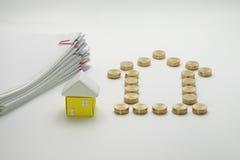 Stos złociste monety i dom z palowym przeciążenie dokumentem Zdjęcie Stock