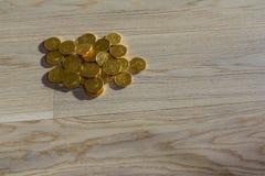 Stos złociste monety na drewnianej podłoga Obrazy Stock