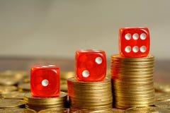 Stos Złote walut monety z Czerwonymi kostka do gry Obrazy Royalty Free