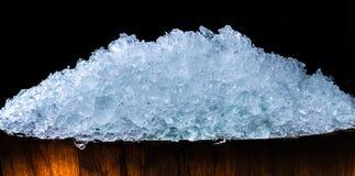 Stos zdruzgotane kostki lodu w drewnianym wiadrze na ciemnym tle z kopii przestrzenią Zdruzgotane kostki lodu pierwszoplanowe dla Fotografia Stock