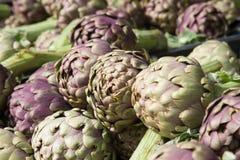 Stos zieleni i purpurowi Włoscy karczochy przy rolnika marke Zdjęcie Stock