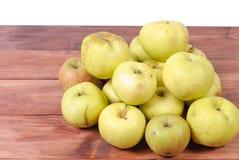 Stos zieleni jabłka kłama na drewnianym tle obrazy stock