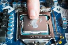 Stosować termiczną pastę z palcem podczas jednostki centralnej Intel i5 instalaci na płycie głównej Obraz Stock