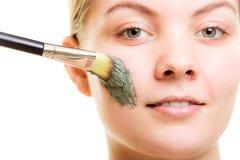 stosowanie opieki skóry przejrzystego lakier Kobieta stosuje glinianą błoto maskę na twarzy obraz royalty free