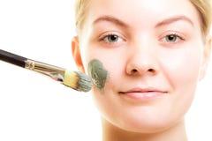 stosowanie opieki skóry przejrzystego lakier Kobieta stosuje glinianą błoto maskę na twarzy obraz stock
