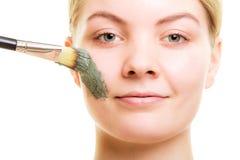 stosowanie opieki skóry przejrzystego lakier Kobieta stosuje glinianą błoto maskę na twarzy obrazy stock