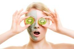 stosowanie opieki skóry przejrzystego lakier Kobieta w gliny masce z kiwi na twarzy fotografia royalty free