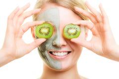 stosowanie opieki skóry przejrzystego lakier Kobieta w gliny masce z kiwi na twarzy obraz stock