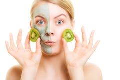 stosowanie opieki skóry przejrzystego lakier Kobieta w gliny masce z kiwi na twarzy fotografia stock