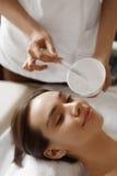 stosowanie opieki skóry przejrzystego lakier Piękna kobieta Dostaje kosmetyk maskę Przy zdroju salonem Zdjęcia Stock