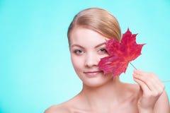 stosowanie opieki skóry przejrzystego lakier Portret młodej kobiety dziewczyna z czerwonym liściem klonowym obraz stock