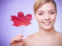 stosowanie opieki skóry przejrzystego lakier Portret młodej kobiety dziewczyna z czerwonym liściem klonowym zdjęcie royalty free