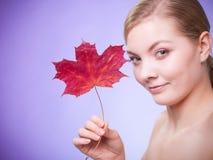 stosowanie opieki skóry przejrzystego lakier Portret młodej kobiety dziewczyna z czerwonym liściem klonowym Obrazy Stock