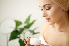 stosowanie opieki skóry przejrzystego lakier Studio strzelający piękna młoda kobieta stosuje moistur zdjęcie royalty free