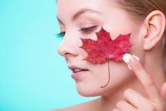 stosowanie opieki skóry przejrzystego lakier Twarz młodej kobiety dziewczyna z czerwonym liściem klonowym obraz royalty free