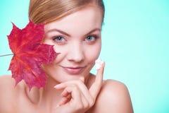 stosowanie opieki skóry przejrzystego lakier Twarz młodej kobiety dziewczyna z czerwonym liściem klonowym obraz stock