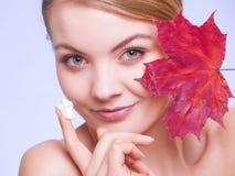 stosowanie opieki skóry przejrzystego lakier Twarz młodej kobiety dziewczyna z czerwonym liściem klonowym obrazy royalty free