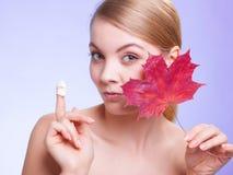 stosowanie opieki skóry przejrzystego lakier Twarz młodej kobiety dziewczyna z czerwonym liściem klonowym zdjęcie royalty free