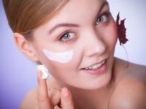 stosowanie opieki skóry przejrzystego lakier Twarz młodej kobiety dziewczyna z czerwonym liściem klonowym zdjęcia stock