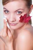 stosowanie opieki skóry przejrzystego lakier Twarz młodej kobiety dziewczyna z czerwonym liściem klonowym fotografia stock