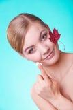 stosowanie opieki skóry przejrzystego lakier Twarz młodej kobiety dziewczyna z czerwonym liściem klonowym obrazy stock