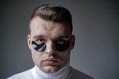 stosowanie opieki sk?ry przejrzystego lakier Bagatelizuje porywistość i zmniejsza ciemnych okręgi Oko łaty dla mężczyzn Mężczyzna fotografia royalty free
