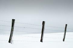 Stosy i drut kolczasty w śnieżnych łąkach Zdjęcia Royalty Free