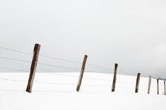 Stosy i drut kolczasty w śnieżnych łąkach Obrazy Stock