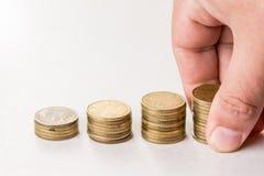 Stosy metal monety nad biały tła i ręki mienia stos monety Fotografia Royalty Free