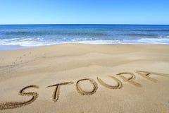Stoupa geschrieben auf den Strand Lizenzfreie Stockfotos