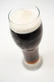 Stout, dark beer. Beer, stout with head, product shot on grey background, cold beer royalty free stock images