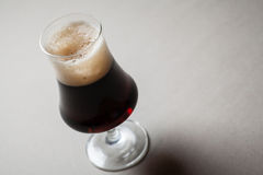 Stout on gray. Tulip glass full of dark stout beer on a gray table Royalty Free Stock Images