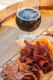 Stout and jerky. Glass of dark stout beer served with lean meat snacks on a wooden barrel Stock Photography